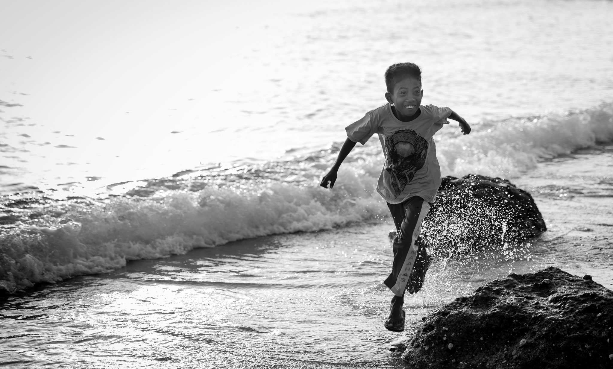 Indonesia - kid running at Pantai Kilo Lima by Travis Longmore